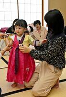 韓国で正月に新調する衣装・ソルビムを着る子ども=佐賀市天神のアバンセ