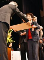 九州地方更生保護委員会の関口裕委員長(左)から表彰状を受け取る保護司=佐賀市の東与賀文化ホールふれあい館