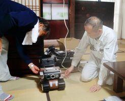 床下点検ロボットを準備する佐賀古民家再生協会の岩宗和人理事長(右)=佐賀市川副町