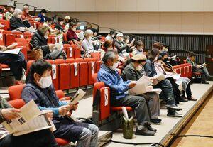 歌詞を見ながら、コンサートを聴く参加者の様子=神埼市の市中央公民館
