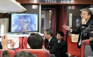 JR新八代駅をすぎ、接続線で軌間変換装置の上をゆっくりと通過するフリーゲージトレインの車内。台車のモニター画像を見ながら国交省鉄道局技術開発室の岸谷克己室長(右)が解説した