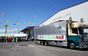 出荷を祝う出席者に見送られて出発する七夕コシヒカリを積んだトラック=白石町のJAさが白石地区の倉庫