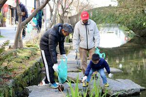 水の中に落ちているゴミを拾う参加者たち=佐賀市の松原川