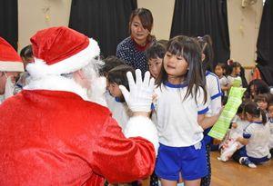 プレゼントを受け取った後サンタとハイタッチする園児=基山町の基山保育園