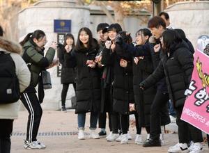 23日、韓国・浦項の試験会場前で、後輩ら(右側)に激励される受験生(共同)
