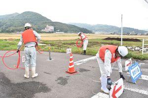 牟田辺遊水地(後方)内を通る道路を通行止めにする手順を確かめる協力業者=多久市南多久町