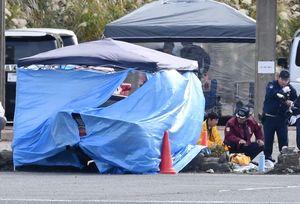 ブルーシートに囲まれた事故車両周辺を調べる警察官=12日午後0時55分、佐賀市富士町の天山スキー場駐車場
