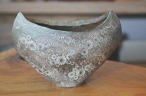 大小の菊文様が散りばめられた「三島手扁花入れ」。登り窯で釉薬をかけず焼成した作品で、薪の灰が自然釉となっている