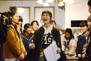 参加者らに、童謡「かえるの合唱」を歌うよう指示する下尾苑佳さん=唐津市の旧唐津銀行
