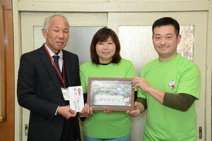 記念写真と寄付金を手渡した鏡山小卒業生の田代国章さん(右)と中尾留美さん(中央)。左は礎靖久校長=唐津市の同校