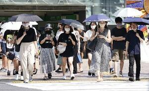 強い日差しが照り付ける中、日傘を差して東京・渋谷を歩くマスク姿の女性ら=5日午後