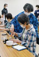講師の西津倫子さん(手前から2人目)からお茶の作法を学ぶ参加者たち=吉野ヶ里町のふれあい館