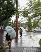 台風の影響で強風や雨が降り、傘を押さえて通勤する人の姿も目についた=5日午前7時41分、佐賀市城内