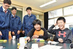 出前授業で小学生に簡易ロボットの製作を教える有田工高の生徒たち=伊万里市の黒川小学校