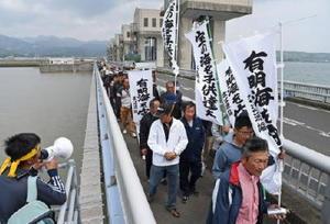 排水門(奥)の開門を訴え、潮受け堤防上を行進する漁業者ら。左は調整池=27日午前、長崎県諫早市