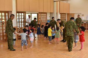 園児とゲームを楽しむ陸上自衛隊水陸機動団の隊員=伊万里市山代町のさくら保育園