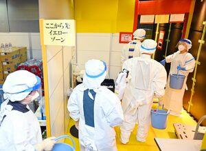 防護服を着て消毒作業に向かう佐賀県職員=20日午前、佐賀市のアパホテル佐賀駅前中央