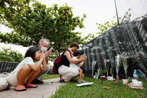 慰霊の日を迎え、沖縄戦犠牲者の氏名が刻まれた「平和の礎」に手を合わせる遺族=23日午後、沖縄県糸満市の平和祈念公園