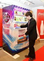 設置された自動販売機でコカ・コーラを購入する茨城国体eスポーツ佐賀県代表の大石晃德さん=佐賀市白山の佐賀新聞文化センター