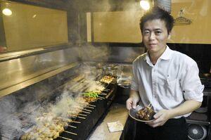 熱気に包まれる焼き場で、串を焼き上げる井上絢矢さん=7月、福岡県久留米市