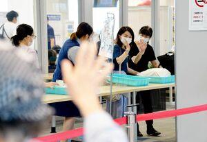 保安検査場前で手を振り、見送る人との別れを惜しむ羽田便の搭乗客=14日午後、佐賀市川副町の佐賀空港