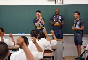 個人チャントで歓迎され、笑みをこぼす原川力選手(左)とビクトル・イバルボ選手(中央)=基山町の東明館高