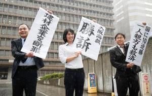 建設アスベスト訴訟の控訴審判決で、大阪高裁前で掲げられた「勝訴」などと書かれた垂れ幕=20日午後