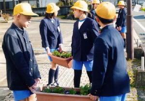 花苗を植えたプランターを運ぶ子どもたち=神埼市脊振支所前