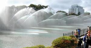 大勢の通行人が足を止めて見入った、佐賀市消防団の五色放水=佐賀市の佐賀城公園北堀