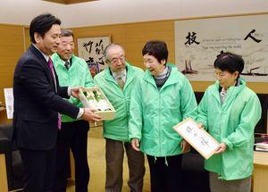 山口知事(左)にしぼりたての地酒「鎮西八郎」を贈った上峰町民有志=佐賀県庁