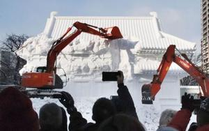 重機で取り壊される奈良・薬師寺の大講堂の雪像=13日、札幌市