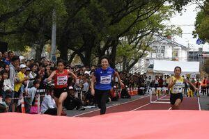 小学生と50メートル競走で勝負する木村文子選手(中央)=佐賀市の本丸通り