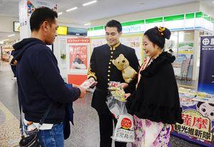 駅利用者にリーフレットを渡す西郷隆盛と篤姫役のメンバー=佐賀市