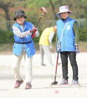 グラウンドゴルフ 力強くボールを打ち込む上峰町の選手(左)=佐賀市の大和中央公園自由広場