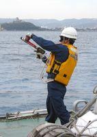 ロープを投射する近距離もやい銃を構える海上保安官