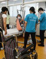 リフトを使ったベッドからの移動を体験する民生委員=神埼市の神埼清明高