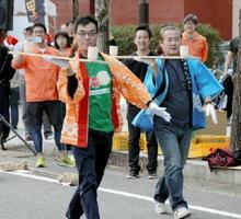 皿板に乗せた素焼きの器を慎重に運ぶ参加者=有田町のJR有田駅前
