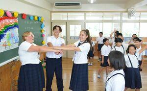 児童と交流し笑顔を見せる左から、ケンドラさん(17)、アンドリューさん(16)、ケイラさん(15)=佐賀市の金立小