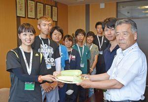 佐賀大学農学部の学生らが道の駅への出荷に向けて開発した白いトウモロコシを受け取る田島町長(右)=白石町役場