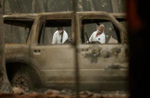 米カリフォルニア州の山火事の焼け跡を捜索する人々=15日(AP=共同)