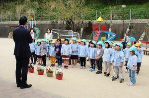 贈呈式で、村上大祐市長(左)から花苗を贈られた嬉野りすの森保育園の園児たち=嬉野市塩田町(嬉野市提供)