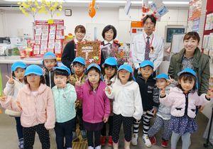 記念品などを手渡し、記念写真に収まるちとせ保育園の園児たちと千歳郵便局の局員=神埼市千代田町の千歳郵便局