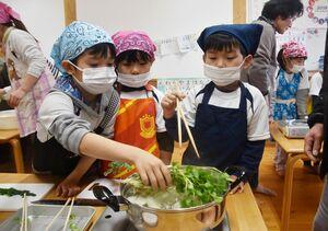 自分たちで収穫した野菜を入れ、七草がゆを作る園児たち=佐賀市富士町の北部保育園