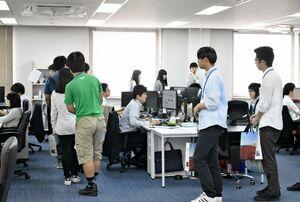 システム開発現場を見学する参加者ら=佐賀市の木村情報技術