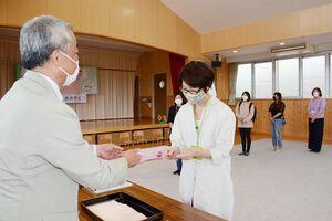 支援金の入った封筒を保護者に渡す峯晋園長(左)=佐賀市の龍谷こども園