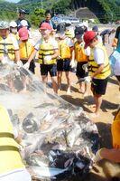網にかかった魚を見て喜ぶ児童たち=唐津市の幸多里の浜