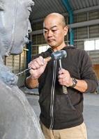 鍋島直正像の原型を微調整する德安和博さん=佐賀市川副町のミゾタ川副事業所