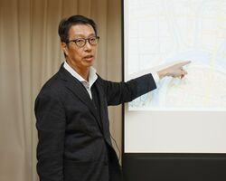 次期広域ごみ処理施設の建設予定地周辺の地図を示しながら話す島谷幸宏・九州大学大学院教授=鳥栖市の本町会館