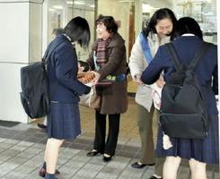 学生らにパンフレットを配布し啓発する国際ソロプチミスト佐賀有明の会員=佐賀駅