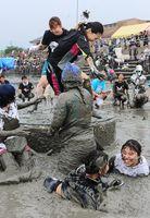 女性限定の押し相撲「HAKKEYOI」。小さな土俵から次々に干潟に落ちる参加者=鹿島市の七浦海浜スポーツ公園